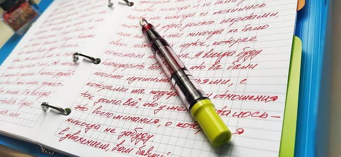 Крупным планом записи, сделанные чернилами Pierre Cardin Matryoshka Red и лежащая перьевая ручка TWSBI Eco T