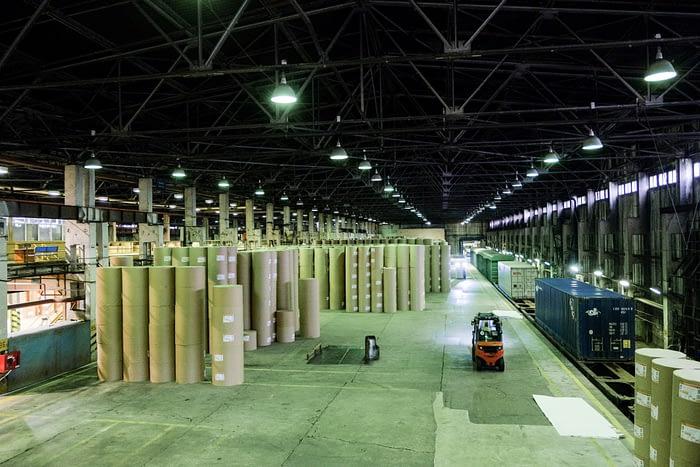 Фотография цеха отгрузки готовой продукции. Огромное пемещение уходящее в даль, а в нём стоят под потолок пирамиды из бумажных ролей