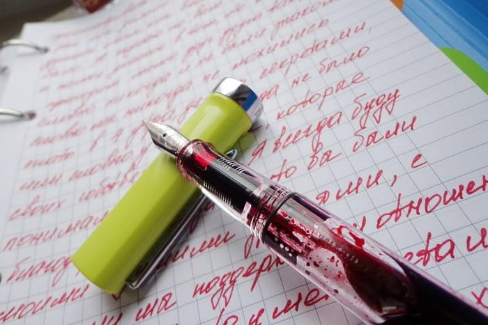 TWSBI Eco T крупный план, а на заднем плане записи чернилами Pierre Cardin Matryoshka Red