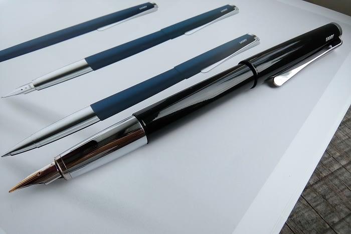 На каталоге LAMY лежит перьевая ручка LAMY Studio Piano Black со снятым колпачком и обнажённым пером F.