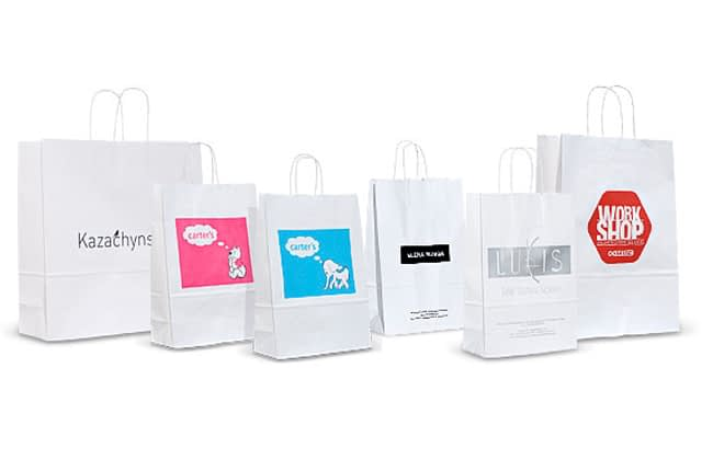 На фотографии несколько пакетов из отбеленного крафт с нанесенными цветными логотипами
