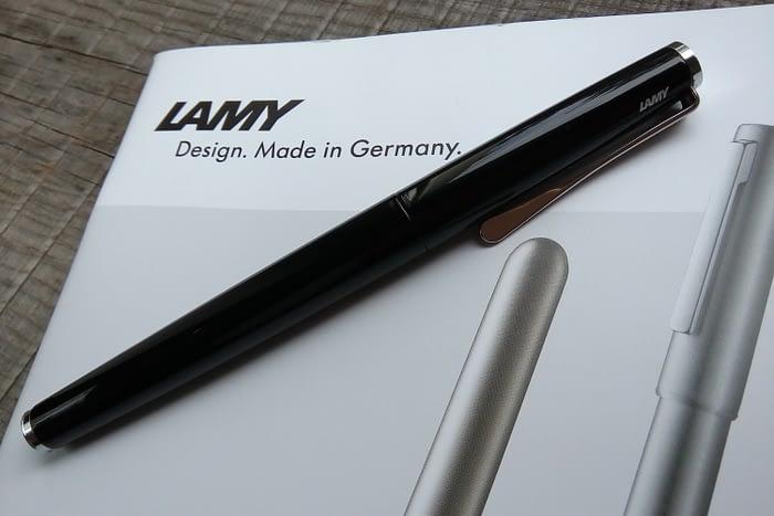 перьевая ручка LAMY Studio Piano Black на фоне каталога с ручками LAMY